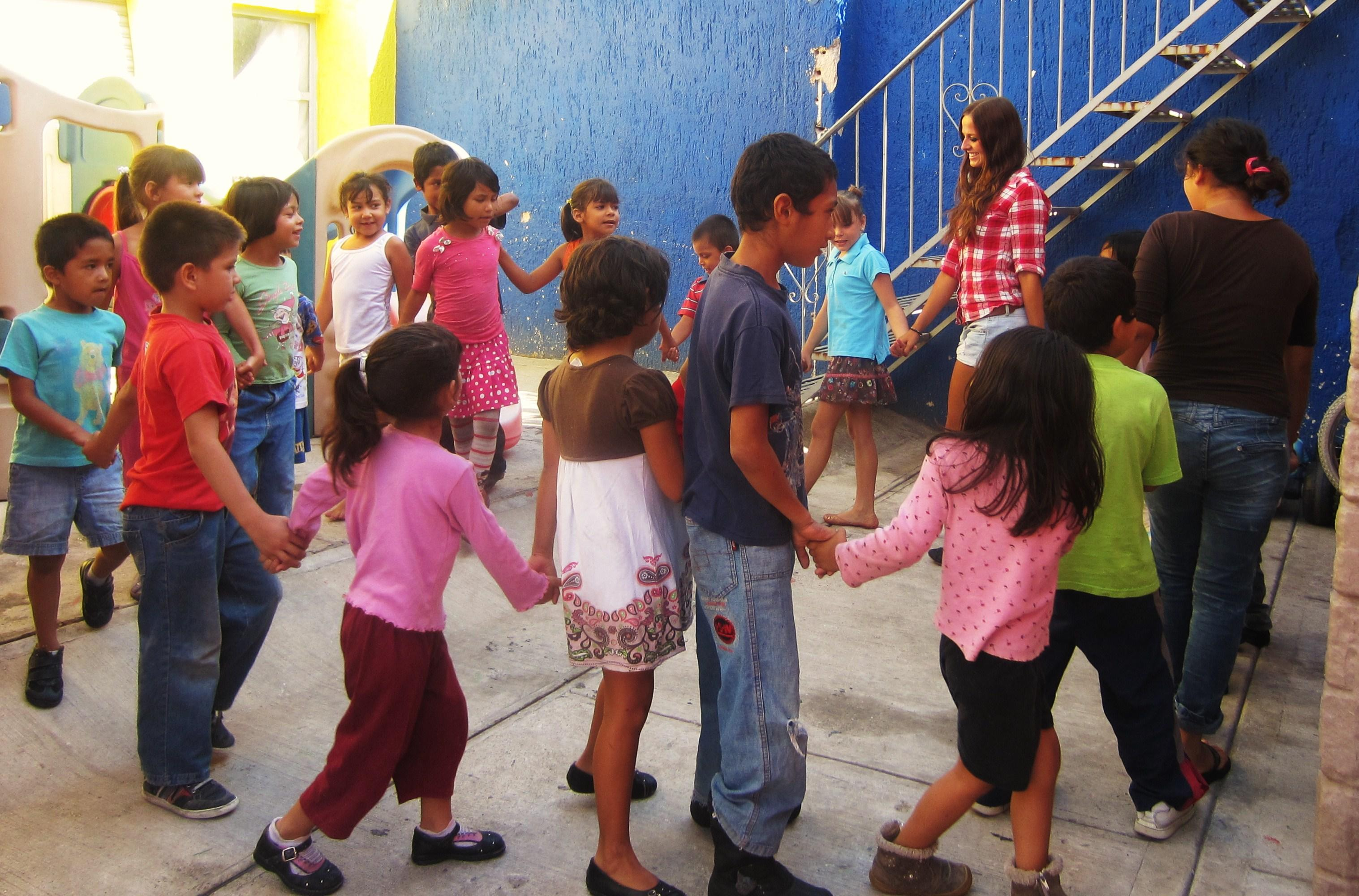 A group of Projects Abroad volunteers working with children in Mexico hold children's hands during an activity at a care centre.